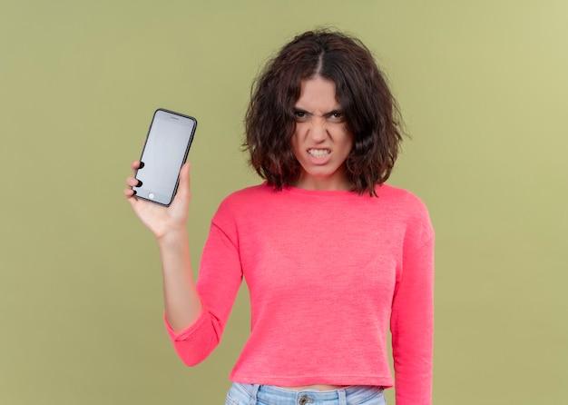 Boze jonge mooie vrouw die mobiele telefoon op geïsoleerde groene muur houdt