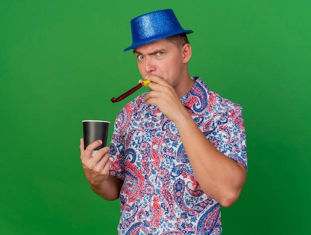 Boze jonge partijkerel die blauwe hoed draagt die kop van koffie houdt en partijventilator blaast die op groene achtergrond wordt geïsoleerd