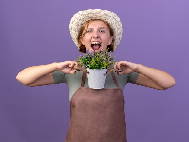 Boze jonge slavische vrouwelijke tuinman die tuinieren hoed draagt die bloemen in bloempot houdt die op purpere muur met exemplaarruimte wordt geïsoleerd