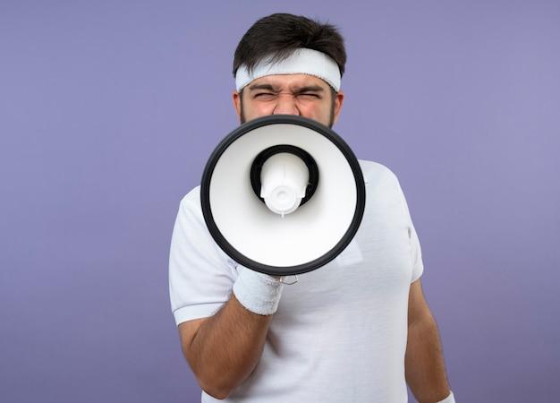 Boze jonge sportieve man met hoofdband en polsbandje spreekt op luidspreker geïsoleerd op groene muur