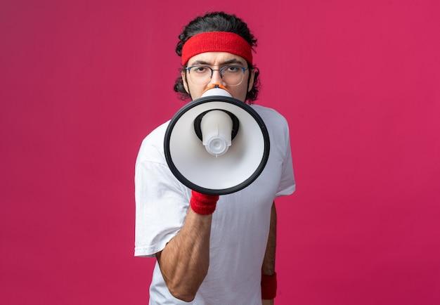 Boze jonge sportieve man met hoofdband met polsbandje spreekt op luidspreker