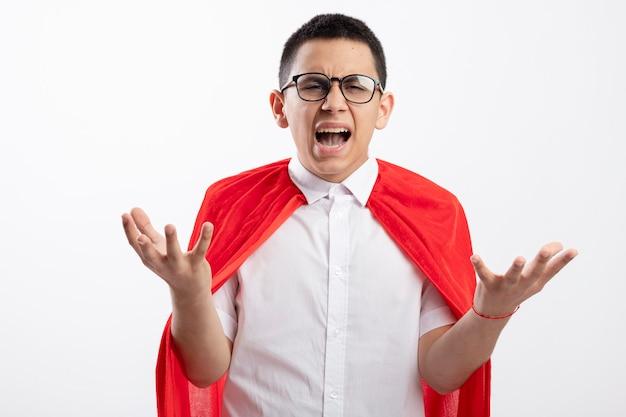Boze jonge superheld jongen in rode cape bril kijken camera weergegeven: lege handen geïsoleerd op een witte achtergrond