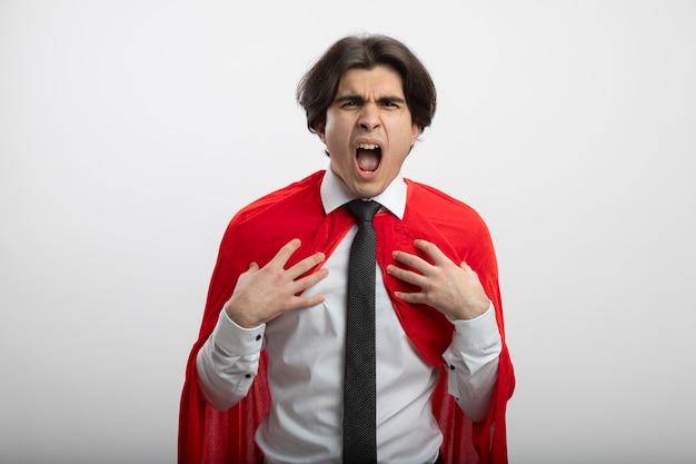Boze jonge superheld man kijken camera dragen stropdas handen zetten borst geïsoleerd op wit