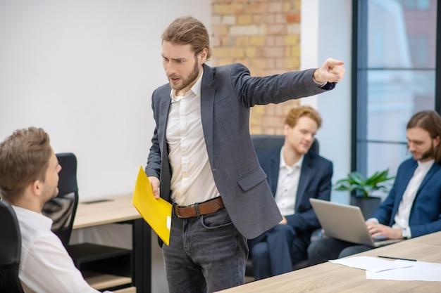 Boze jonge volwassen man in pak met gele map gebaren naar vergadering collega in kantoor