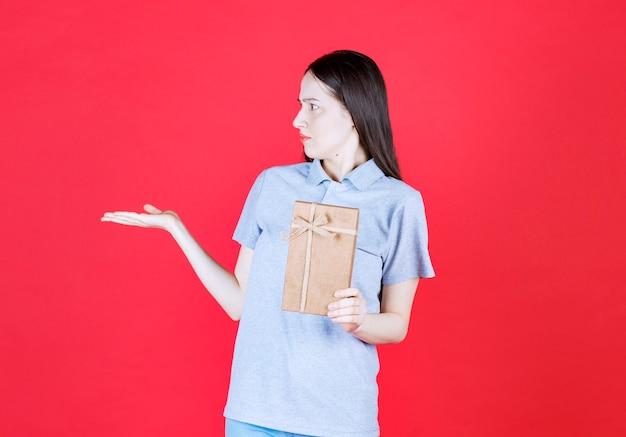 Boze jonge vrouw die een geschenkdoos vasthoudt en wegkijkt