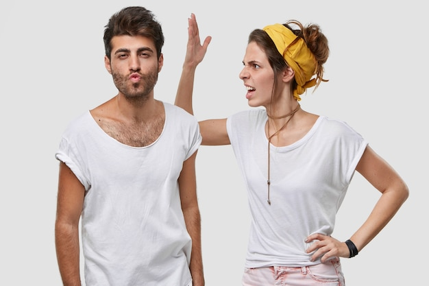 Boze jonge vrouw draagt een gele hoofdband, een casual wit t-shirt, steekt de hand op en benadert iets wat haar man ziet, kijkt negatief, vraagt om niet voor gek te spelen, heeft een verkeerd begrip of ruzie