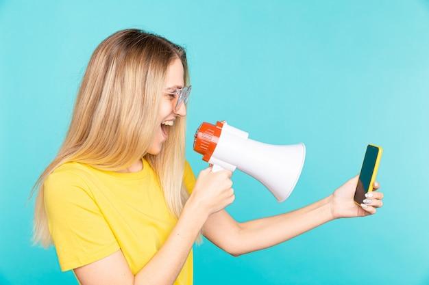 Boze jonge vrouw in geel overhemd schreeuw met megafoon naar mobiele telefoon op blauw