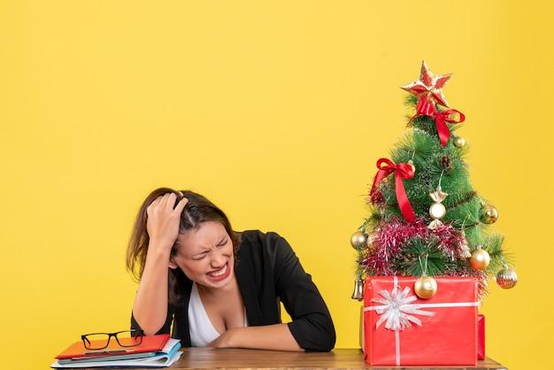Boze jonge vrouw in pak in de buurt van versierde kerstboom op kantoor op geel