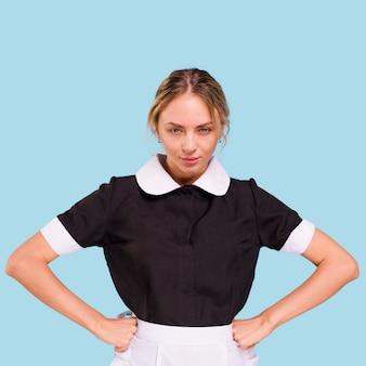 Boze jonge vrouw met handen op haar taille die zich tegen blauwe achtergrond bevindt