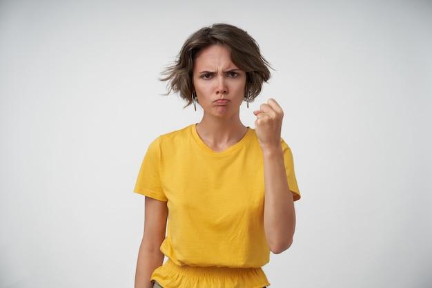 Boze jonge vrouw met kort kapsel dreigt met opgeheven vuist terwijl ze boos kijkt, casual kleding draagt terwijl ze staat