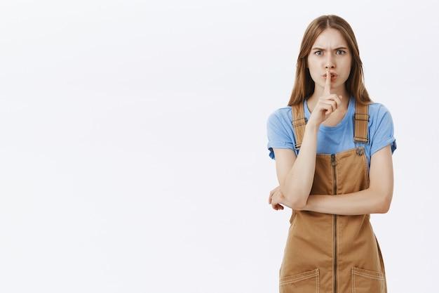 Boze jonge vrouw zwijgt en fronst gehinderd, heeft stilte nodig, maakt shh-gebaar