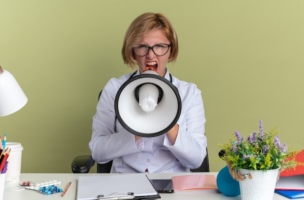 Boze jonge vrouwelijke arts met medische mantel met bril en stethoscoop zit aan tafel met medische hulpmiddelen spreekt op luidspreker geïsoleerd op olijfgroene muur