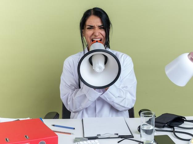 Boze jonge vrouwelijke arts met medische mantel met stethoscoop zit aan bureau met medische hulpmiddelen spreekt op luidspreker geïsoleerd op olijfgroene muur