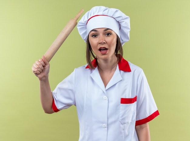Boze jonge vrouwelijke kok die chef-kok uniform draagt die deegroller opheft die op olijfgroene muur wordt geïsoleerd