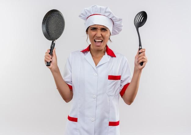 Boze jonge vrouwelijke kok die de pan en de spatel van de chef-kok eenvormige holding op geïsoleerde witte muur met exemplaarruimte draagt