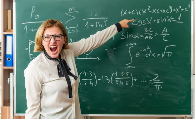 Boze jonge vrouwelijke leraar met een bril die voor de schoolbordpunten staat op het bord in de klas