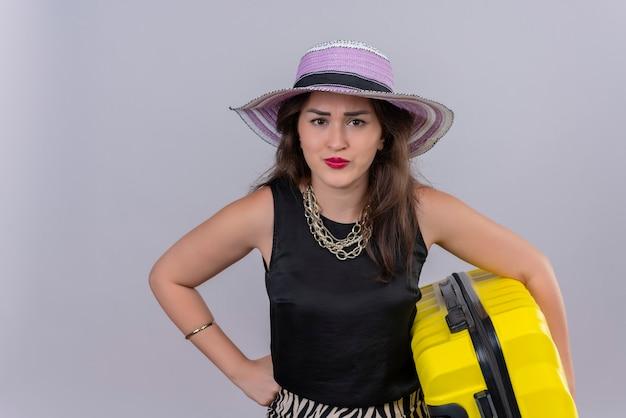 Boze jonge vrouwelijke reiziger die zwart onderhemd in de koffer van de hoedenholding op witte muur draagt