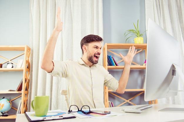 Boze jonge zakenman die in bureau werkt en schreeuwt