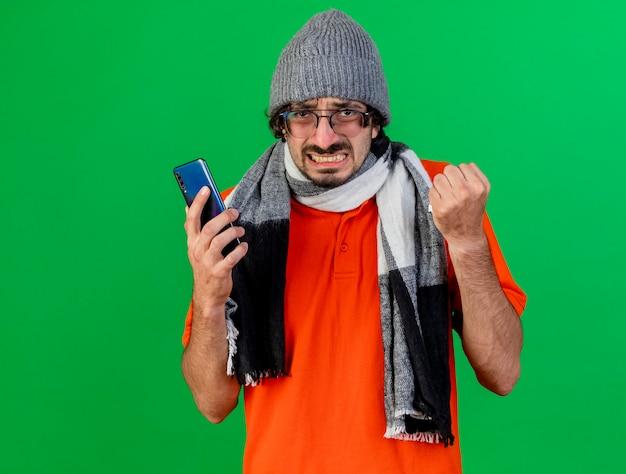 Boze jonge zieke man die de muts en de sjaal van de glazen winter draagt ?? die mobiele telefoon en servet houdt die voorzijde bekijkt die op groene muur wordt geïsoleerd