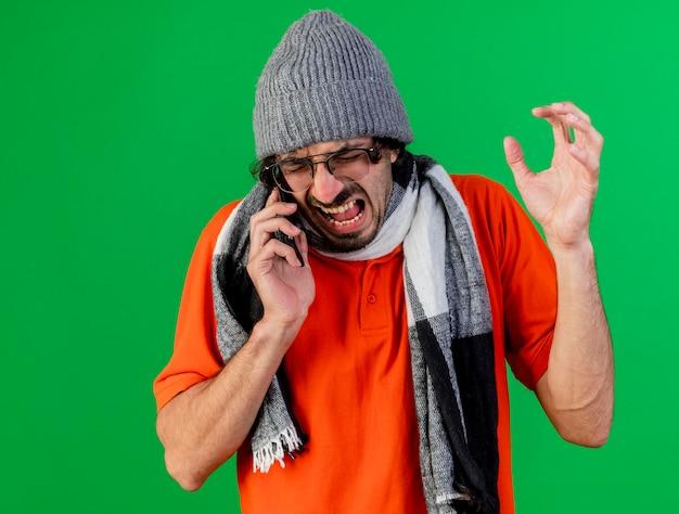 Boze jonge zieke man met bril, muts en sjaal hand in de lucht houden praten aan de telefoon met gesloten ogen geïsoleerd op groene muur