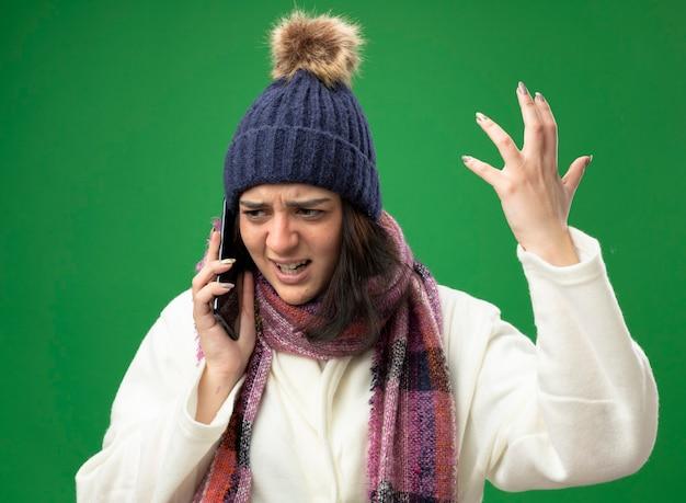 Boze jonge zieke vrouw die de muts en de sjaal van de gewaadwinter draagt ?? die op telefoon spreekt die hand in lucht houdt die kant bekijkt die op groene muur wordt geïsoleerd