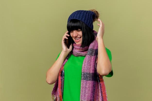 Boze jonge zieke vrouw die de wintermuts en sjaal draagt die op telefoon spreekt die hand in lucht houdt met gesloten ogen die op olijfgroene muur met exemplaarruimte wordt geïsoleerd