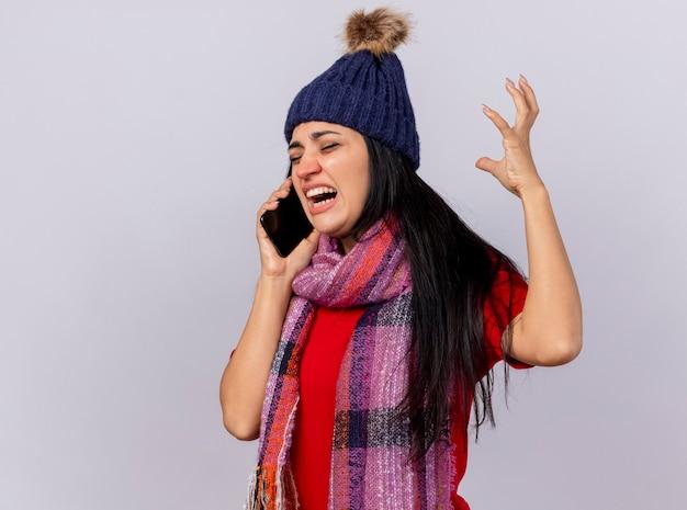 Boze jonge zieke vrouw die de wintermuts en sjaal draagt die zich in profielmening bevindt die op telefoon spreekt die hand in lucht houdt met gesloten ogen die op witte muur wordt geïsoleerd