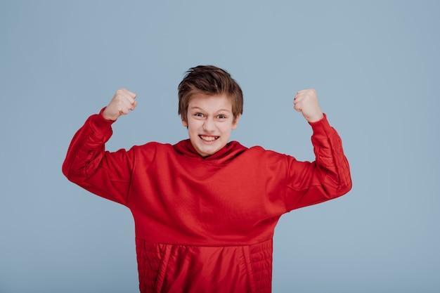 Boze jongen jongen in rood sweatshirt met handen omhoog geïsoleerd op blauwe achtergrond kopie ruimte