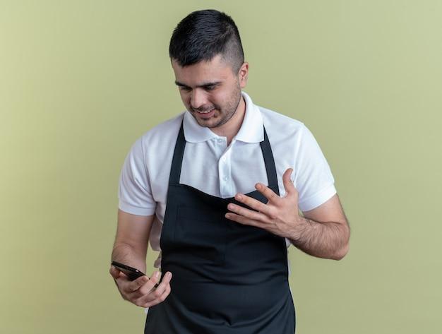 Boze kappersman in schort met smartphone die ernaar kijkt en verontwaardigd zijn arm opsteekt