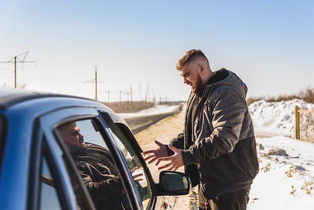 Boze kerel dichtbij de gebroken auto in rusland