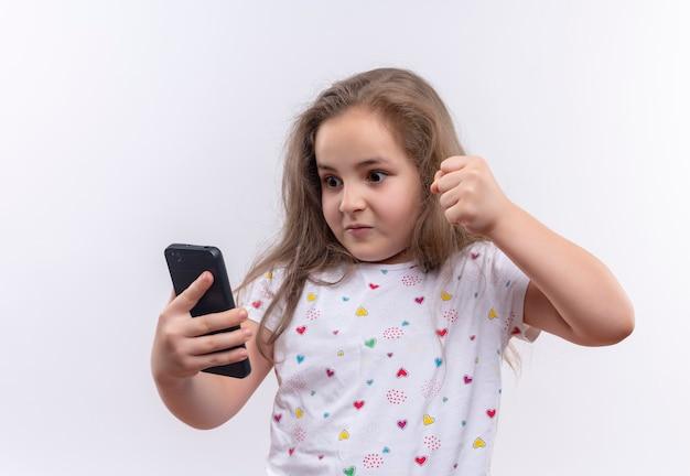 Boze kleine schoolvrouw die de witte telefoon van de t-shirtholding en opgeheven vuist op geïsoleerde witte muur draagt
