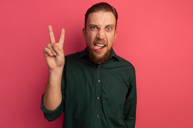 Boze knappe blonde man steekt tong uit en gebaren overwinning handteken geïsoleerd op roze muur