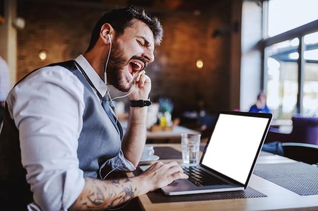 Boze knappe kaukasische elegante zakenman in pak met video-oproep via laptop zittend in café.