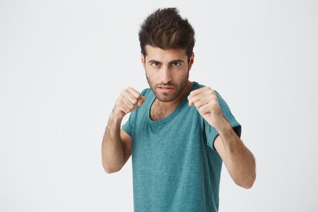 Boze knappe ongeschoren jonge spaanse man in trendy blauwe tshirt, trendy kapsel, geconcentreerde expressie, training met bokszak voor bokswedstrijden.