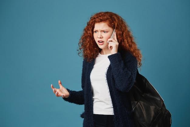 Boze knappe studentenvrouw die, expressief gesticulerend met handen opzij kijken, die met moeder over studie over telefoon debatteren.