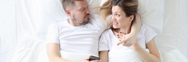 Boze man die de smartphone van zijn vrouw in zijn handen houdt terwijl hij op bed ligt en de telefoon van zijn vrouw bedient