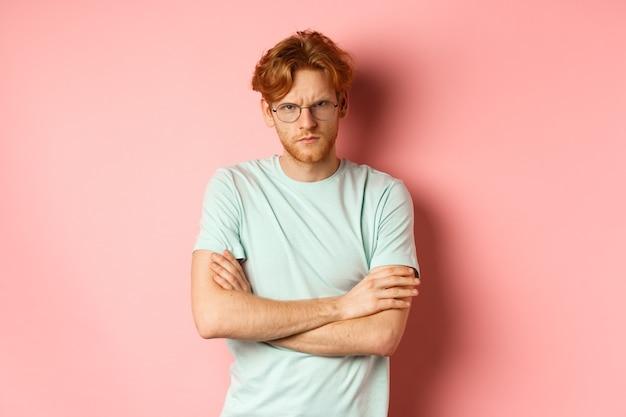 Boze man in bril met rood haar fronsend, kruis armen op borst in defensieve houding, mokkend naar je, staande over roze achtergrond.