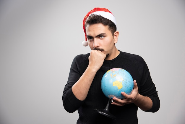 Boze man in de hoed van de kerstman met een vuist en een wereldbol vast te houden.