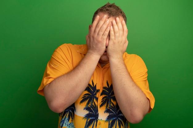 Boze man in glazen en oranje overhemd die zijn gezicht bedekken met handen die zich over groene muur bevinden