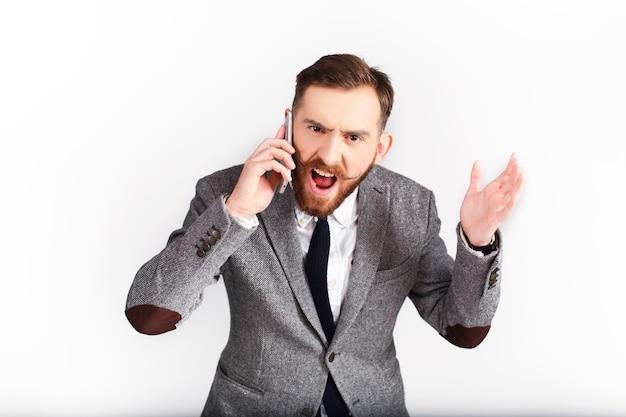 Boze man in grijs pak praat over de telefoon