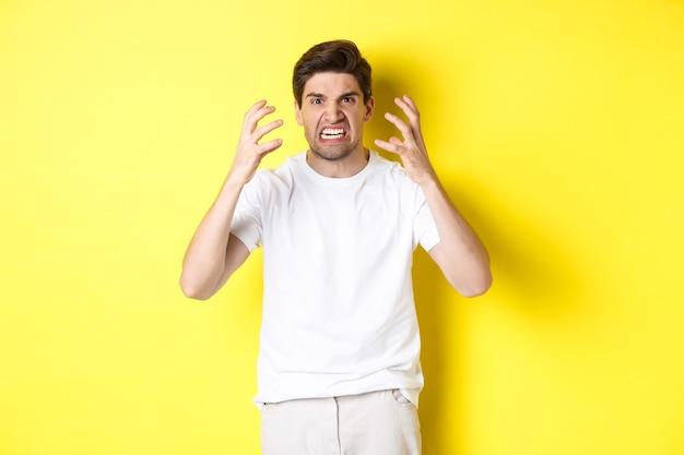 Boze man kijkt boos, grimassen en handen schudden woedend, staande woedend tegen gele muur