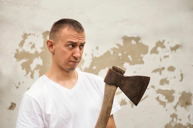 Boze man met een bijl in zijn hand tegen de achtergrond van een armoedige muur
