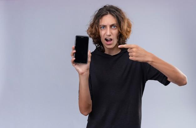 Boze man met lang haar in zwarte t-shirt met een telefoon en wijst naar telefoon op witte muur