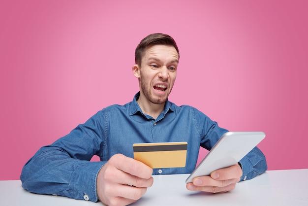 Boze man met plastic kaart kijken naar scherm van smartphone terwijl woede of irritatie geïsoleerd uiten