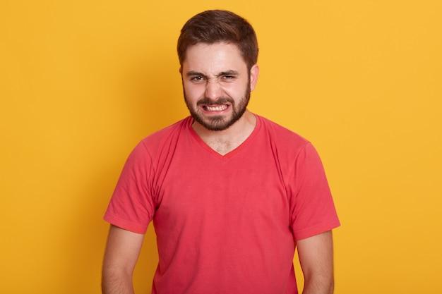 Boze man met rode casual t-shirt, ontevreden, houdt handen gespannen, ongeschoren man met stijlvol kapsel verdraaide zijn gezicht met woede, poseerde geïsoleerd op geel.