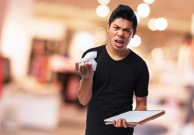 Boze man rippen een blad uit een notebook