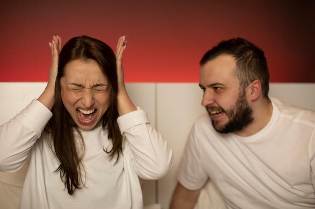 Boze man schreeuwt tegen vrouw tijdens ruzie huilende vrouw houdt hoofd met handen