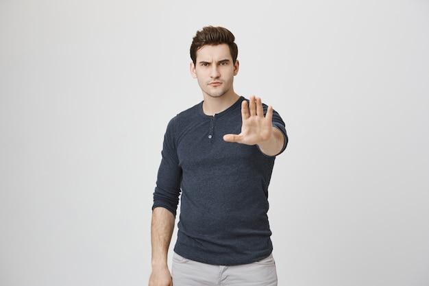 Boze man strekt zijn hand uit, toont stopgebaar, verbiedt of waarschuwt