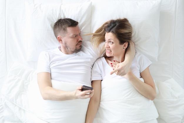 Boze man zijn vrouw smartphone in handen houden