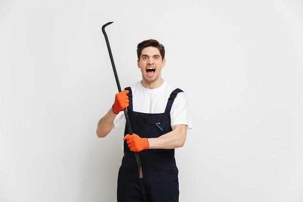 Boze mannelijke bouwer in handschoenen die terwijl koevoet over grijze muur gillen